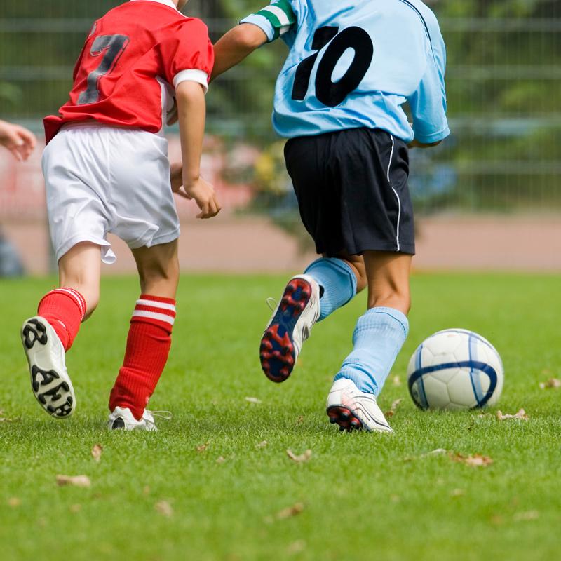 Zwei Jungen spielen Fußball.